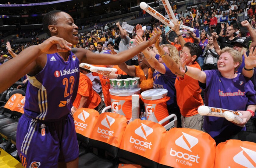 Phoenix Mercury forward Charde Houston celebrates with fans following her team's victory over the Los Angeles Sparks in Game 3 of their WNBA playoff series at Staples Center. Although the WNBA has loyal fans, many clubs struggle to turn a profit.