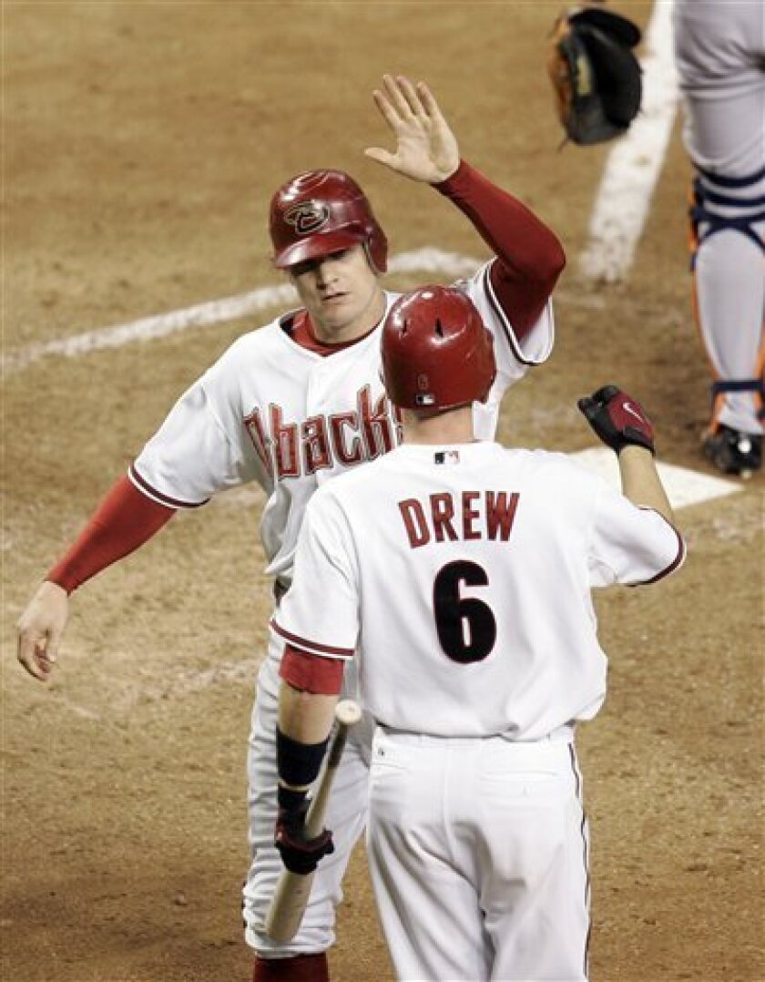 Arizona Diamondbacks' Eric Byrnes high fives teammate Stephen Drew (6) after tying the game during the seventh inning of a baseball game against the Detroit Tigers Friday, May 16, 2008 in Phoenix. (AP Photo/Matt York)