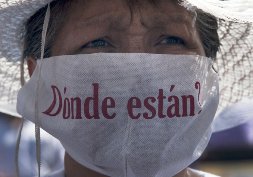 """A mother with a face mask that reads in Spanish """"Where are they?"""" marches along with hundreds of other mothers holding images of their missing relatives during Mother's Day on Sunday in Mexico City."""