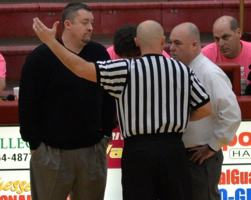 A referee talks to Riverdale Coach Cory Barrett, left, and Smyrna Coach Shawn Middleton during a Feb. 21 high school basketball game in Murfreesboro, Tenn.