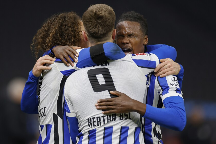 Hertha Berlin's Krzysztof Piatek, center, celebrates scoring his side's second goal with his teammates during the German Bundesliga soccer match between Hertha Berlin and Union Berlin at the Olympic stadium in Berlin, Friday, Dec. 4, 2020. (Odd Andersen/Pool Photo via AP)