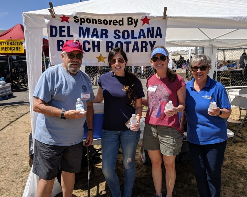 """The Del Mar-Solana Beach Rotary ran the """"Water Tent"""" at Stand Down San Diego for the 12th year in a row. Led by DMSB Rotary past president, Bill Sutton, many Rotarians and friends handed out more than 5,700 bottles of chilled water to homeless veterans, their dependents, and volunteers over the three-day event. The Stand Down is an annual support and intervention event for homeless veterans held at the athletic field of San Diego High School. Civilian volunteers and active duty military personnel provide meals, picture IDs, and sleeping tents, clothing, showers, haircuts and medical, dental and vision assistance along with homeless court, counseling, chaplain services, 12-step meetings, and information about Veterans benefits, employment and job counseling services and shelters. From left, Del Mar-Solana Beach Rotary past president and Marine, Bill Sutton (left), who organized and led 25 other Rotarians and friends in giving chilled water bottles and encouragement at the """"Stand Down San Diego 2019"""" with Rotarians Radia Hunter, Molly Fleming, and Suzanne Sutton. For Stand Down questions, email darcy.pavich@vvsd.net. Visit the Rotary at DMSBRotary.com."""