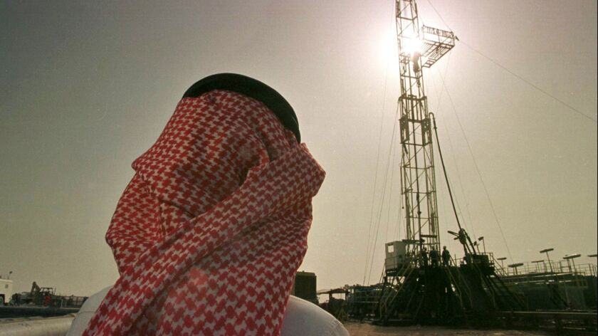 Khaled Otaibi, an official at the Saudi oil company Aramco, watches an oil rig at the Howta oil field in Saudi Arabia.