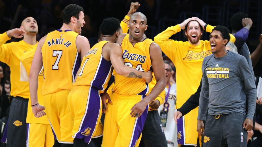 Lakers star Kobe Bryant is mobbed by teammates after scoring 60 points in the final game of his career, a 101-96 victory against the Utah Jazz.