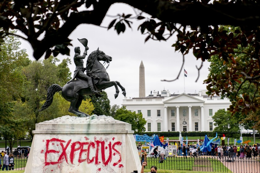 """The words """"Expect Us"""" are spray painted on the base of the Andrew Jackson statue in Lafayette Park as Indigenous and environmental activists protest in front of the White House in Washington, Monday, Oct. 11, 2021. The words are part of the phrase """"Respect Us, or Expect Us"""" which indigenous women have been using while protesting oil company Enbridge's Line 3 pipeline through Minnesota. President Joe Biden on Friday issued the first-ever presidential proclamation of Indigenous Peoples Day, lending the most significant boost yet to efforts to refocus the federal holiday celebrating Christopher Columbus toward an appreciation of Native peoples. (AP Photo/Andrew Harnik)"""