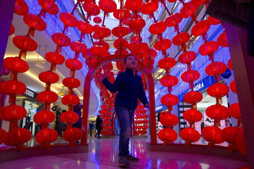 A child walks amongst red lanterns set up for the Spring Festival holidays in Beijing, China, Monday, Feb. 15, 2016. Hopes that the fall in the Chinese currency may have run its course have helped stock markets around the world start the week on a positive note. (AP Photo/Ng Han Guan)
