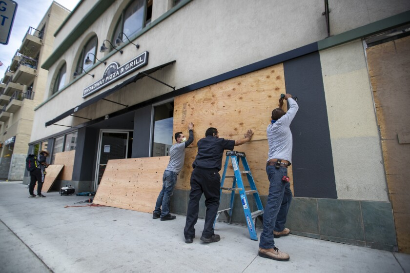 Workers put plywood over windows along Pine Avenue in Long Beach on Monday.