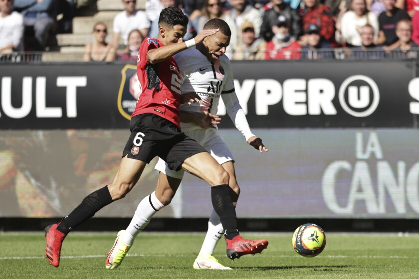 PSG's Kylian Mbappe, rear, is challenged by Rennes' Nayef Aguerd during the French League One soccer match between Rennes and Paris Saint-Germain at the Roazhon Park stadium in Rennes, France, Sunday, Oct. 3, 2021. (AP Photo/Jeremias Gonzales)