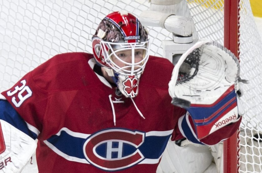 Montreal Canadiens' goalie Mike Condon gloves the puck as they face the Boston Bruins during first period NHL hockey action, in Montreal, on Saturday, Nov. 7, 2015. (Paul Chiasson/The Canadian Press via AP)