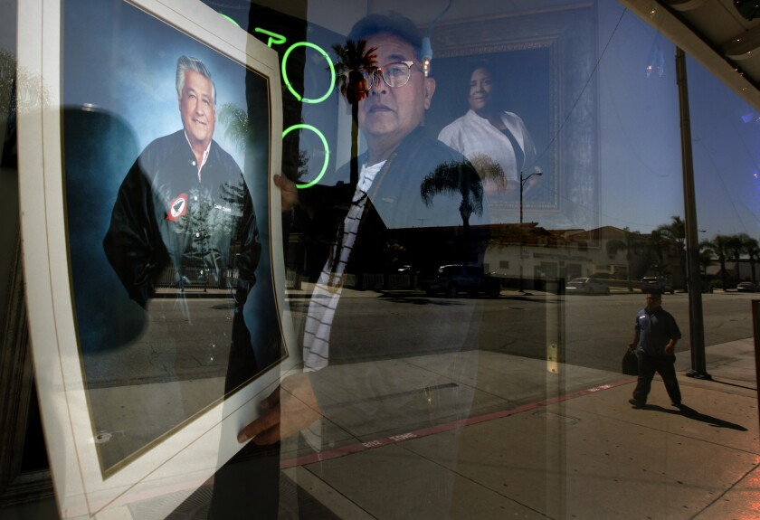 Gary Miyatake, a Japanese American photographer, places his portrait of Cesar Chavez in the display window at his studio in Gardena. The portrait will be donated to the Smithsonian.
