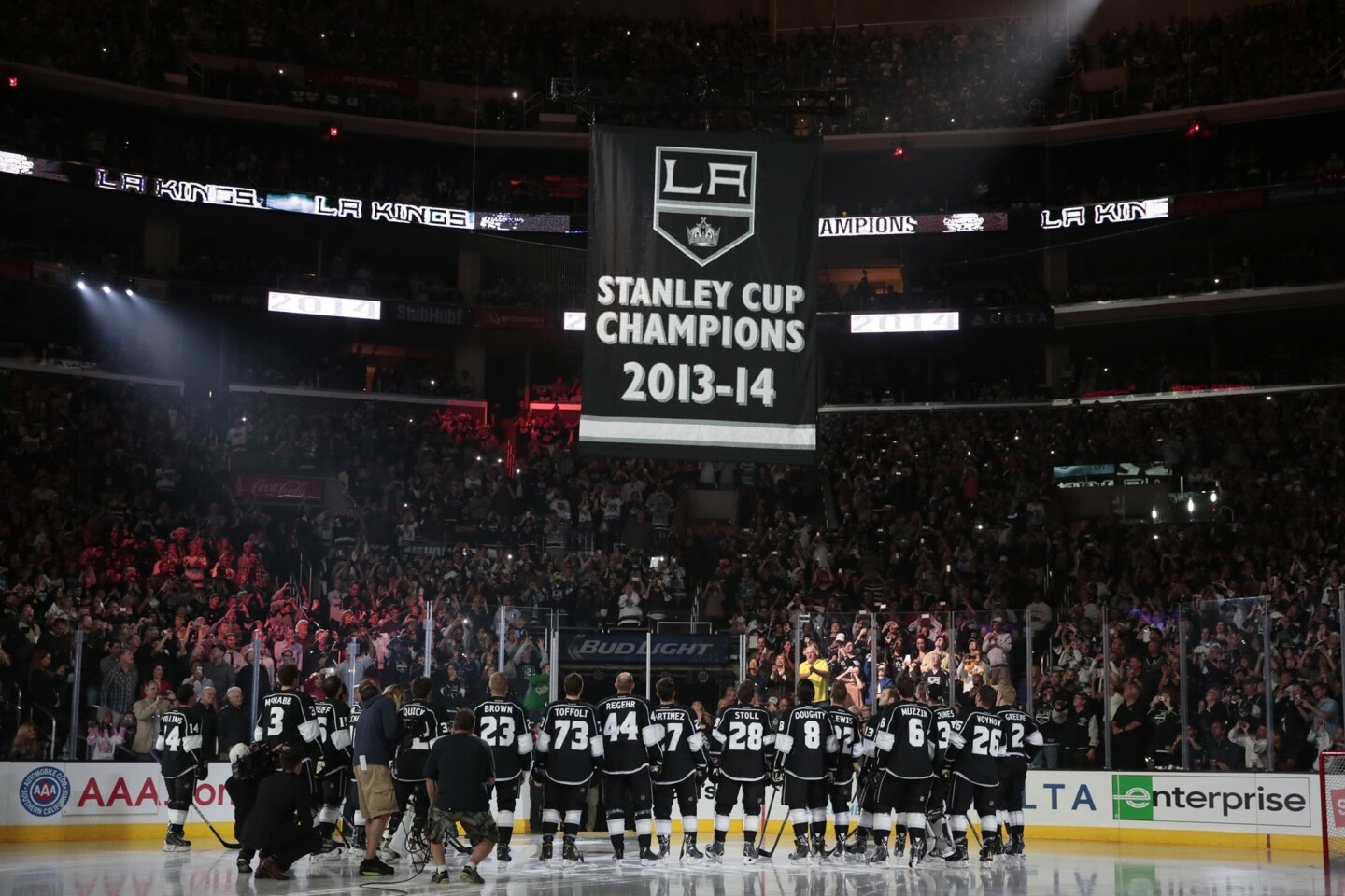 A banner honoring the Kings' 2013-14 Stanley Cup championship is lifted to the Staples Center rafters prior to the team's season 2014-15 season opener against the San Jose Sharks on Wednesday.