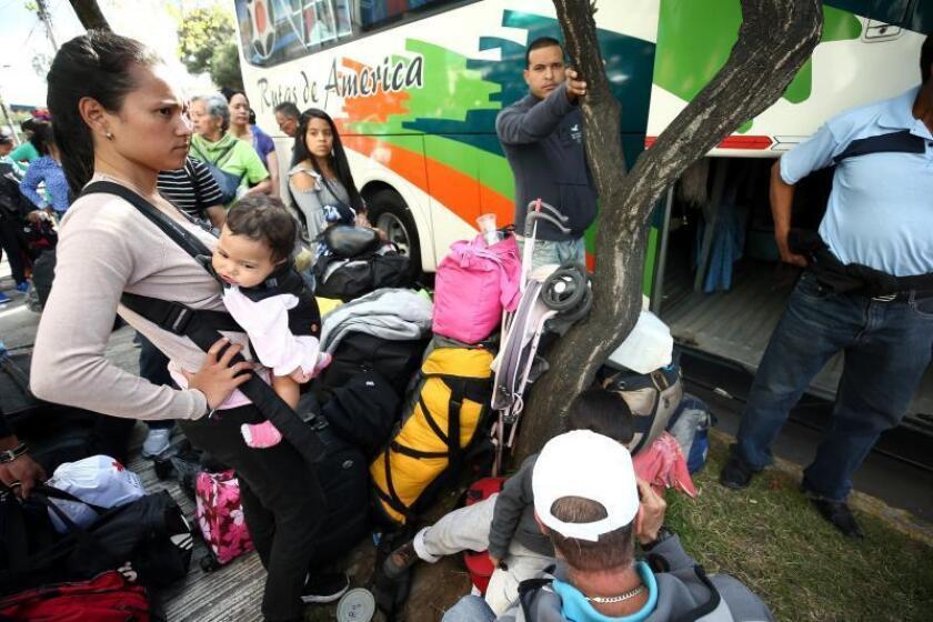 Venezuelan migrants opting for repatriation from Ecuador board buses outside Venezuela's embassy in Quito on Friday, Feb. 1. EFE-EPA/ Jose Jacome