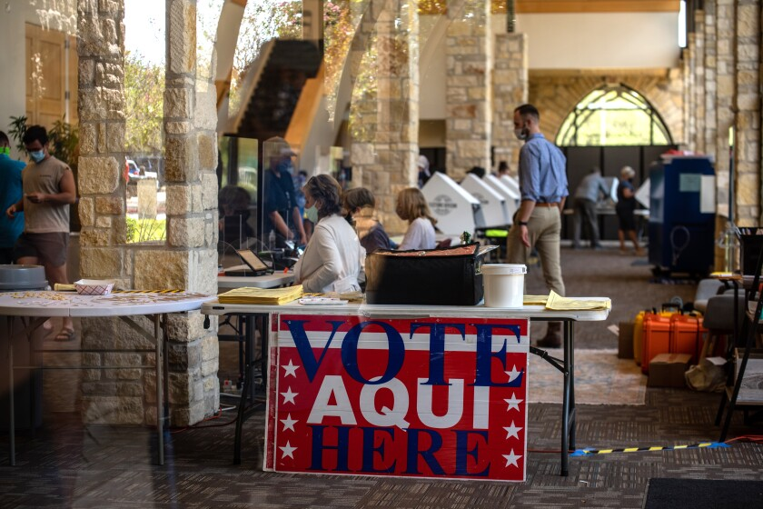 "Volunteers help early voters cast ballots at a busy courtyard polling site in Austin, Texas. A sign reads ""Vote aquí/here."""