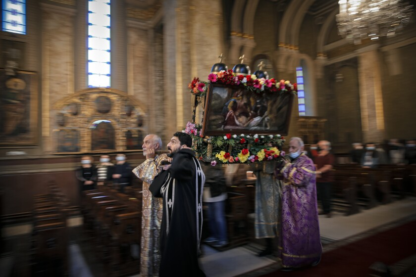 Clergymen carry a structure symbolizing the tomb of Jesus Christ during a Good Friday religious service, at the Armenian Church in Bucharest, Romania, Friday, April 30, 2021. (AP Photo/Vadim Ghirda)