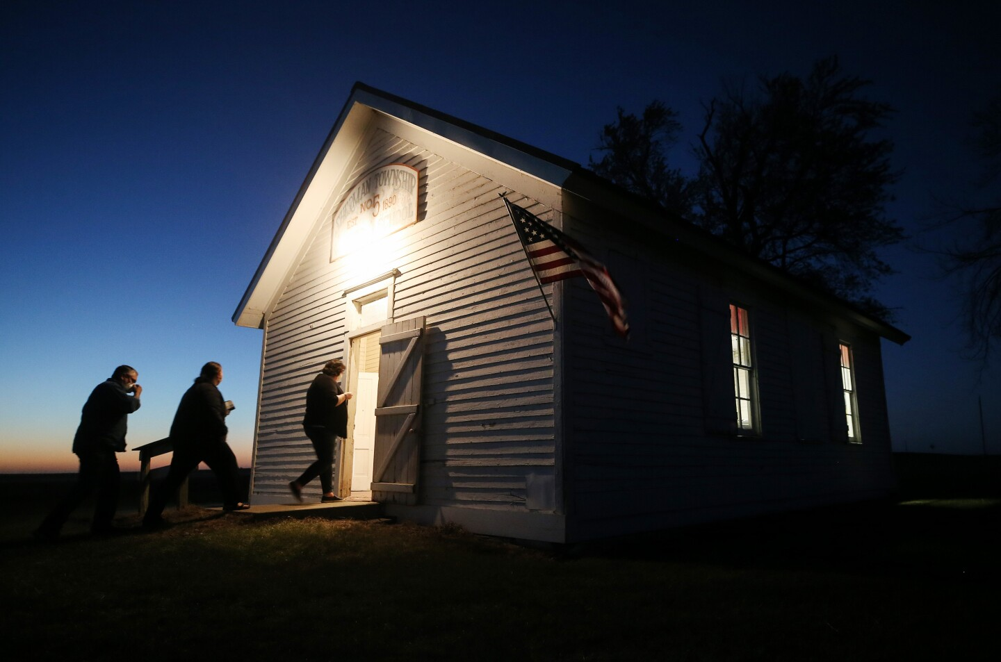 Voters enter a polling place at dusk to cast their ballots at Sherman Township Hall.