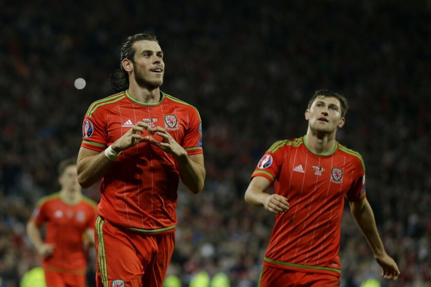 FILE - In this Tuesday, Oct. 13, 2015 file photo, Wales' Gareth Bale, left, celebrates scoring his side's second goal with Ben Davies during the Euro 2016 Group B soccer match between Wales and Andorra at Cardiff City stadium in Cardiff. (AP Photo/Matt Dunham, File)