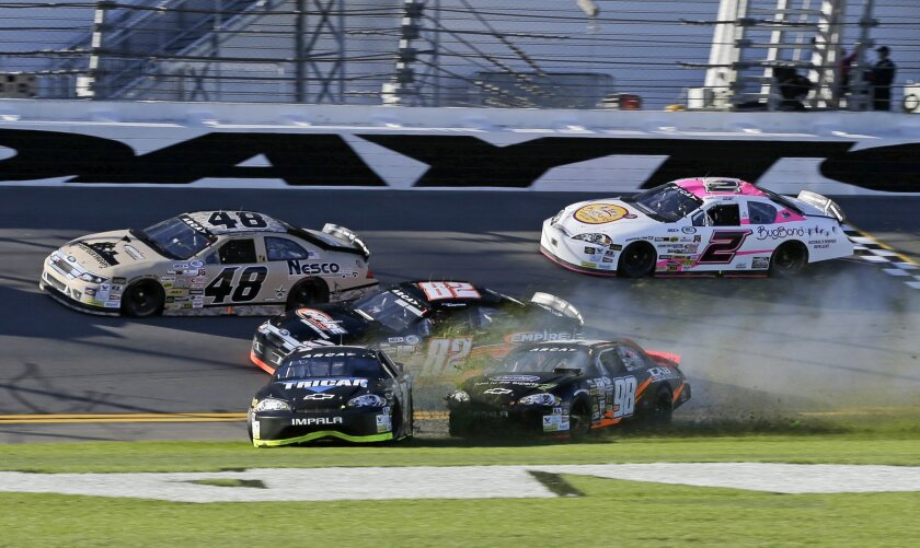 Cole Powell, front left, and Gus Dean (98) wreck on the front stretch during the ARCA series auto race at Daytona International Speedway, Saturday, Feb. 13, 2016, in Daytona Beach, Fla.(AP Photo/Terry Renna)