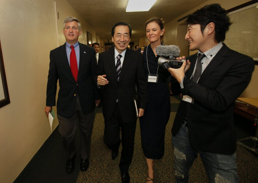 Former Prime Minister of Japan Naoto Kan, center, walks to the conference with San Diego County Supervisor Dave Roberts, left, and his translator Cathy Iwane, right, and one of the many Japanese press. A gathering of experienced nuclear experts convened a conference in San Diego at the chambers o