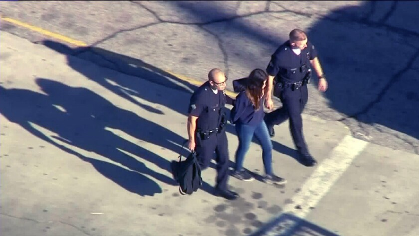 Police take a girl into custody on the campus of Salvador Castro Middle School in Los Angeles follow