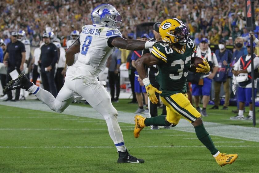 Aaron Jones de los Packers de Green Bay supera a Jamie Collins de los Lions de Detroit para un touchdown, el lunes 20 de septiembre de 2021, en Green Bay, Wisconsin. (AP Foto/Matt Ludtke)