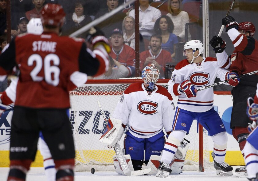 Arizona Coyotes' Michael Stone (26) scores a goal against Montreal Canadiens' Mike Condon, middle, as Canadiens' Alexei Emelin, right, looks for the puck during the first period of an NHL hockey game Monday, Feb. 15, 2016, in Glendale, Ariz. (AP Photo/Ross D. Franklin)