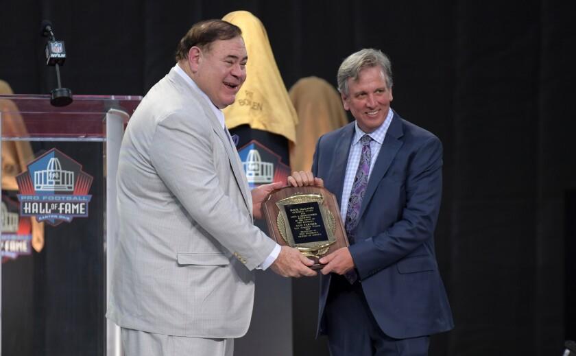 Pro Football Hall of Fame president David Baker hands Sam Farmer the Dick McCann Award.