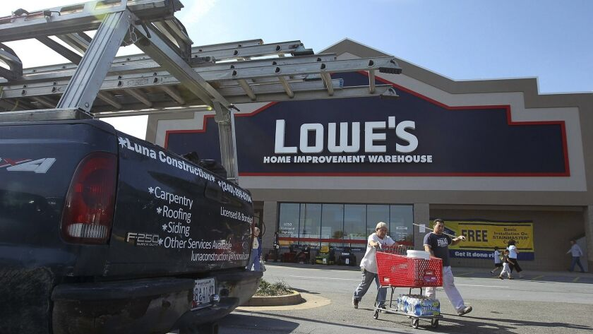 Shoppers emerge from a Lowe's store in 2011. Lowe's said Monday that it will shut down some of its locations.