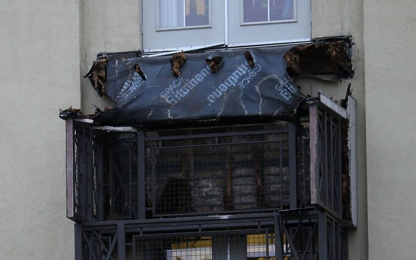A section of collapsed balcony remains on the front of an apartment building in Berkeley.