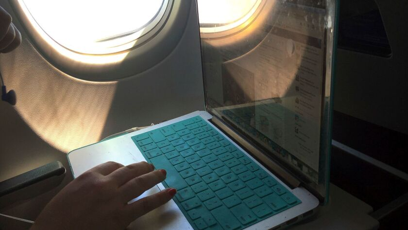 An airline passenger uses a laptop computer during a flight.