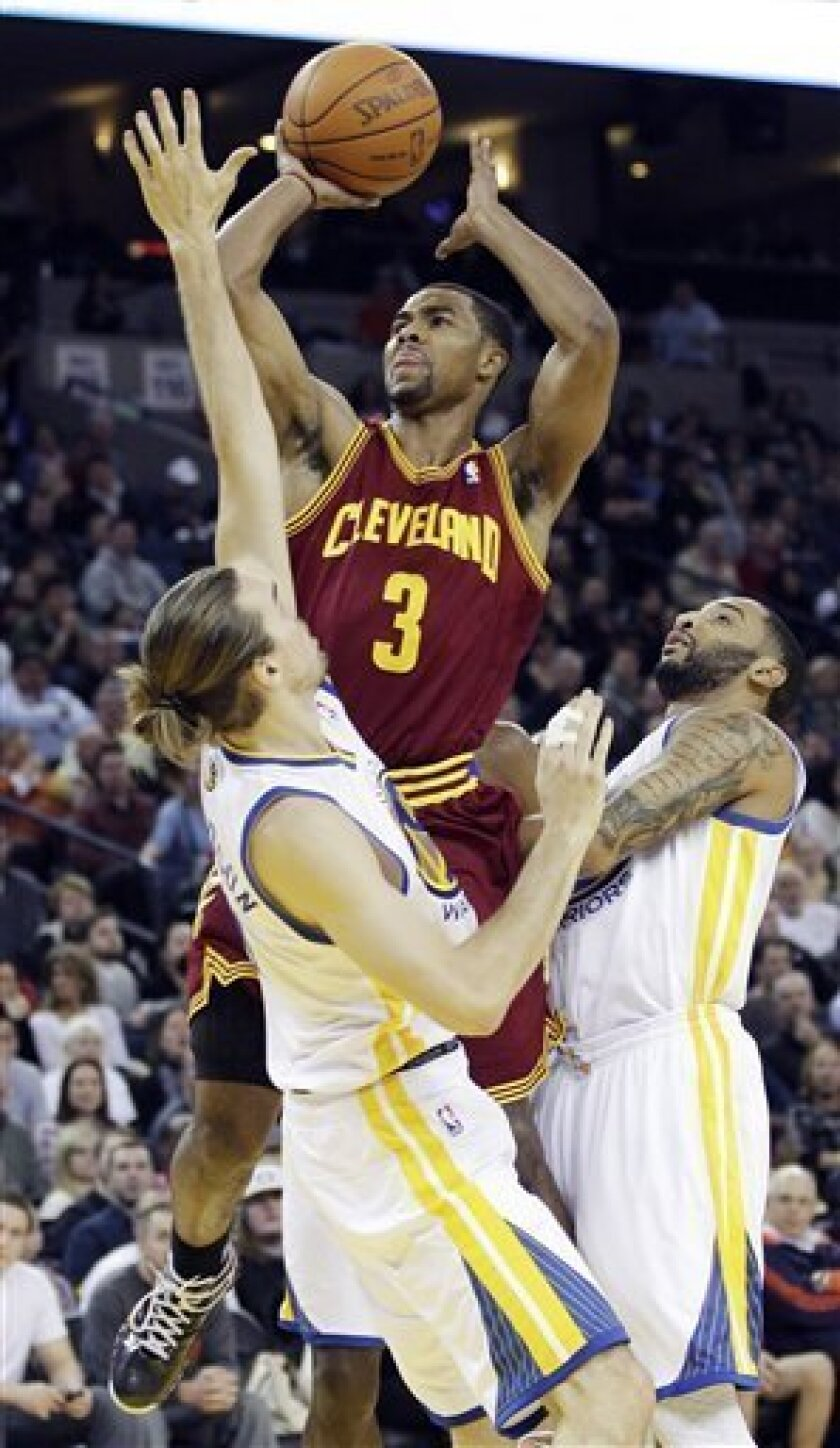 Cleveland Cavaliers' Ramon Sessions (3) shoots over Golden State Warriors' Louis Amundson, left, and Acie Law, right, during the first half of an NBA basketball game in Oakland, Calif., Friday, Jan. 7, 2011. (AP Photo/Marcio Jose Sanchez)