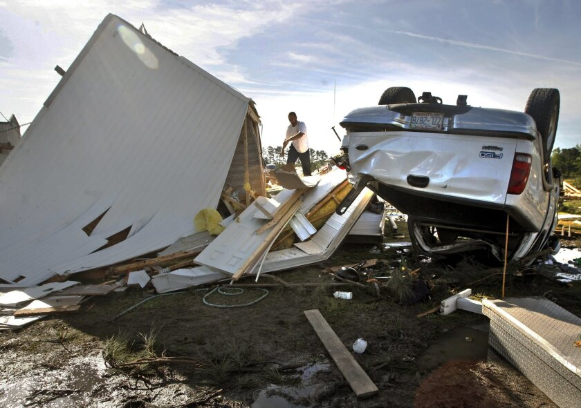 A man tries to salvage belongings from a overturned mobile home in Greenville, N.C. on Saturday, April 26, 2014 after a tornado touched down along Black Jack Simpson Road on Friday. Officials said multiple tornadoes damaged more than 200 homes the previous day and sent more than a dozen people to t
