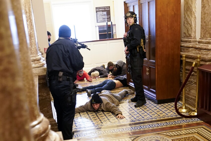 People lie facedown on the floor of the Capitol as police stand over them with weapons.