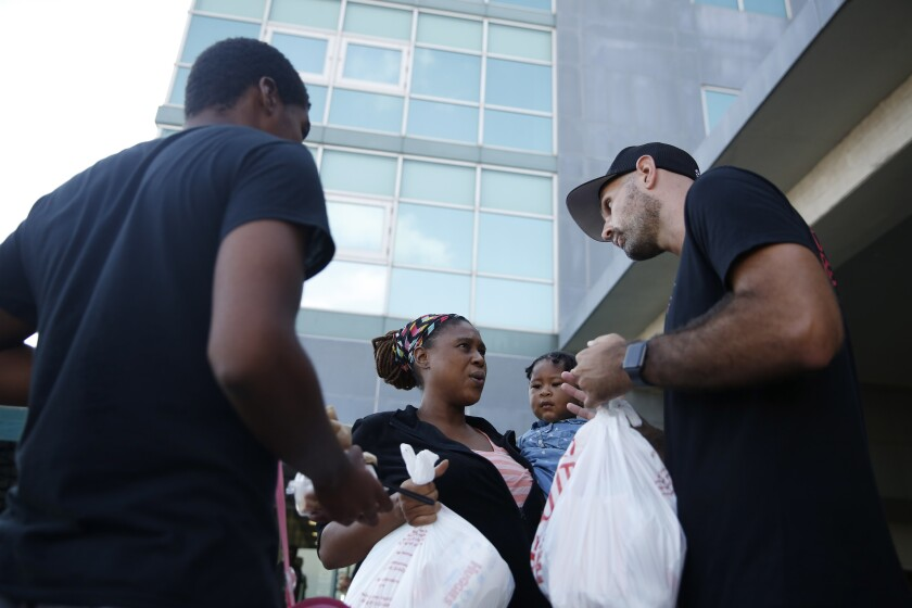"""Volunteer Nick Mills, right, hands Hurricane Dorian evacuee, Leshonda Collins and her 1-year-old daughter Shayniyah, supplies as they arrive from the Grand Celebration cruise ship from Freeport, a city in the Grand Bahamas on Wednesday, Sept. 18, 2019 in Riviera Beach. The cruise ship transported hundreds of evacuees seeking passage from Freeport after the damaged caused by Hurricane Dorian. """"I'm happy to be in the U.S., I'm going to work, work, work, and try to get a job,"""" says Collins. (AP Photo/Brynn Anderson)"""