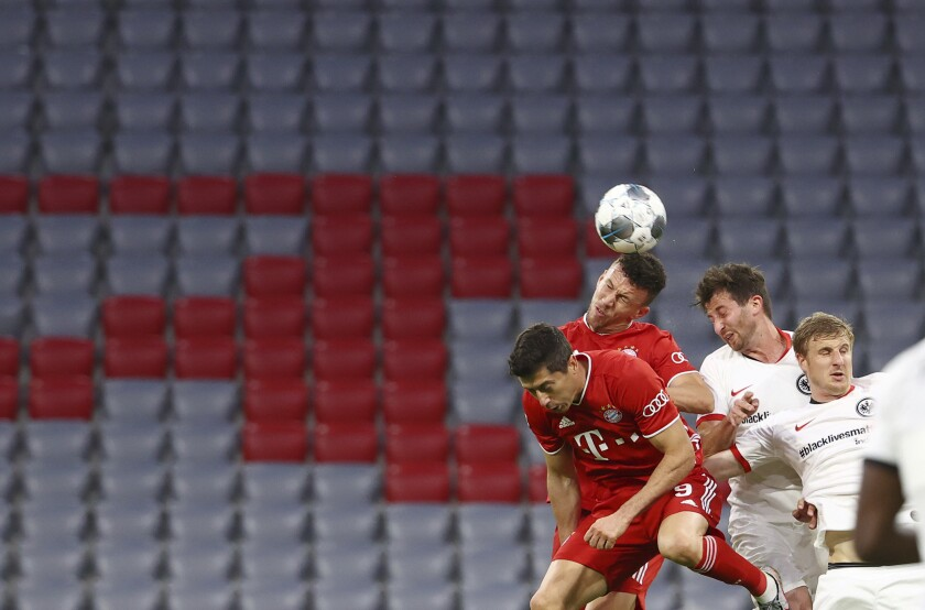 Bayern Munich's Ivan Perisic heads the ball infront of empty stands during the German soccer cup semi-final match between Bayern Munich and Eintracht Frankfurt in Munich, Germany, Wednesday, June 10, 2020. (Kai Pfaffenbach/Pool via AP)