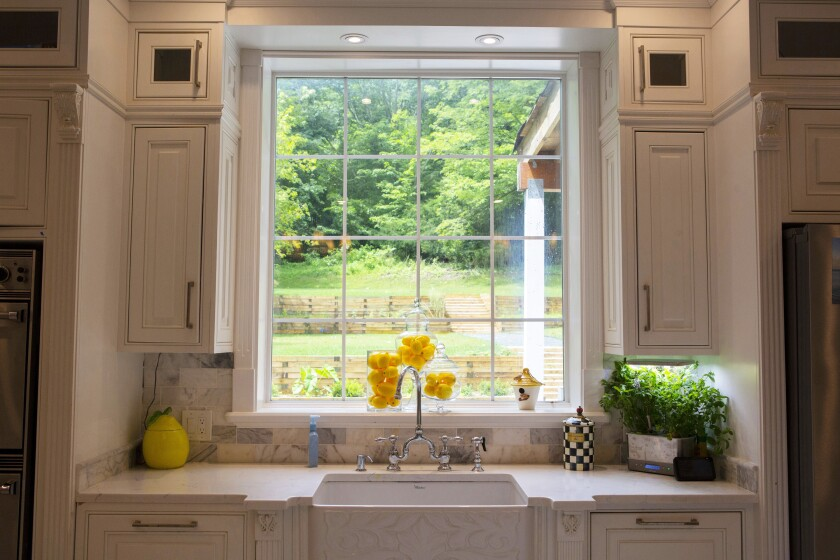 The fireclay kitchen sink features an embossed apron and a bridge faucet.