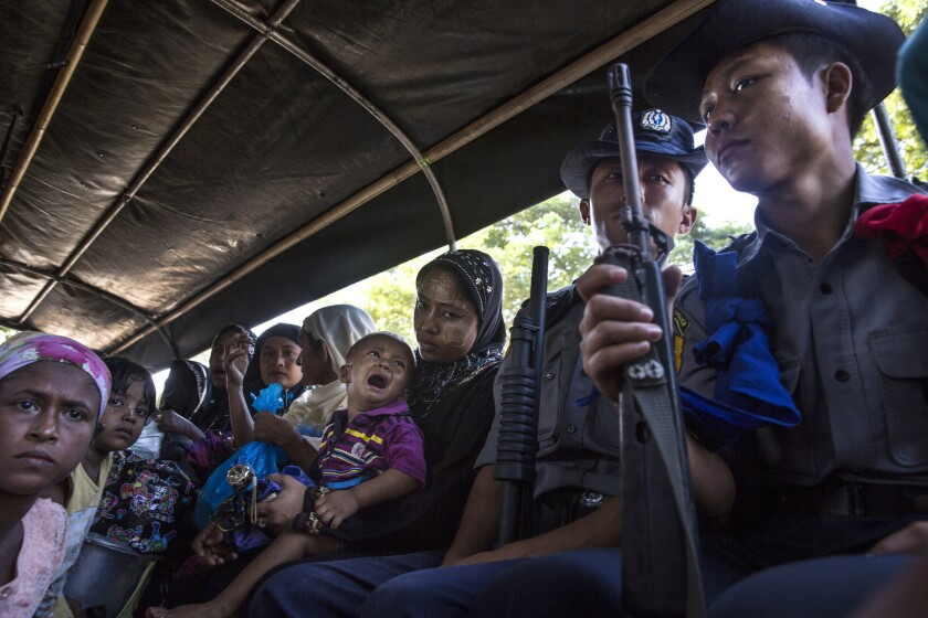 Member's of Burma's Rohingya ethnic minority are escorted by Burmese police in a truck heading back to their remote community of Aung Mingalar.