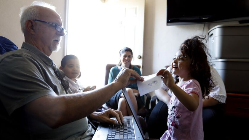 Times columnist Steve Lopez shares paper and pens with Sophia, 4, right, while interviewing her family living in a motel in Pacoima.