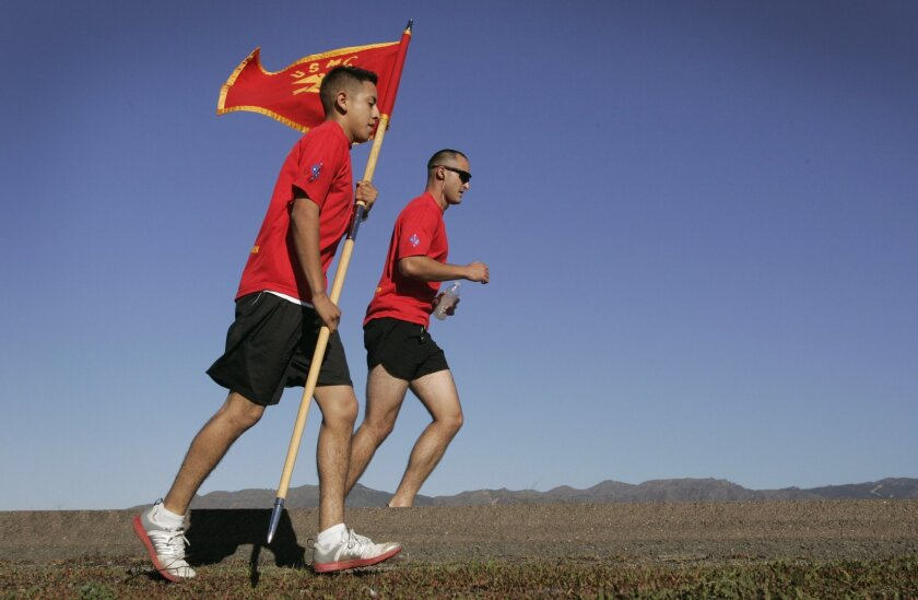 Pvt. First Class Omar Iglesias, foreground, carries a Marine Corps flag, as he runs in the 235-mile relay race at Camp Pendleton, along with Lance Cpl. Bruce Picanso celebrating the 235th birthday of the Marine Corps.