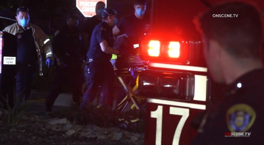 A police officer watches as paramedics roll a gurney carrying a man who was shot by police Friday night in Talmadge.