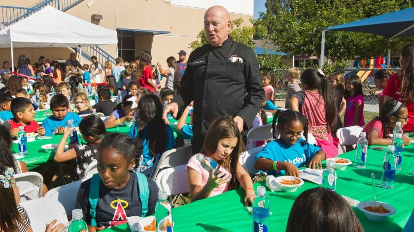 Chef Bruno Serato greets children as they enjoy his pasta at the Boys & Girls Club of Huntington Valley — Pacific Life Foundation Branch in Huntington Beach on Tuesday.