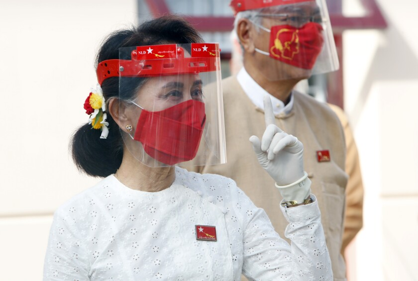 Myanmar leader Aung San Suu Kyi gestures while wearing a face shield, mask and gloves during a flag-raising ceremony to mark the first day of election campaigning at the National League for Democracy party's temporary headquarters in Naypyitaw, Myanmar on Tuesday, Sept. 8, 2020. Myanmar holds a general election on Nov. 8 and began a sixty-day election campaign period Tuesday, which may be disrupted due to a resurgence of the coronavirus. (AP Photo/Aung Shine Oo)