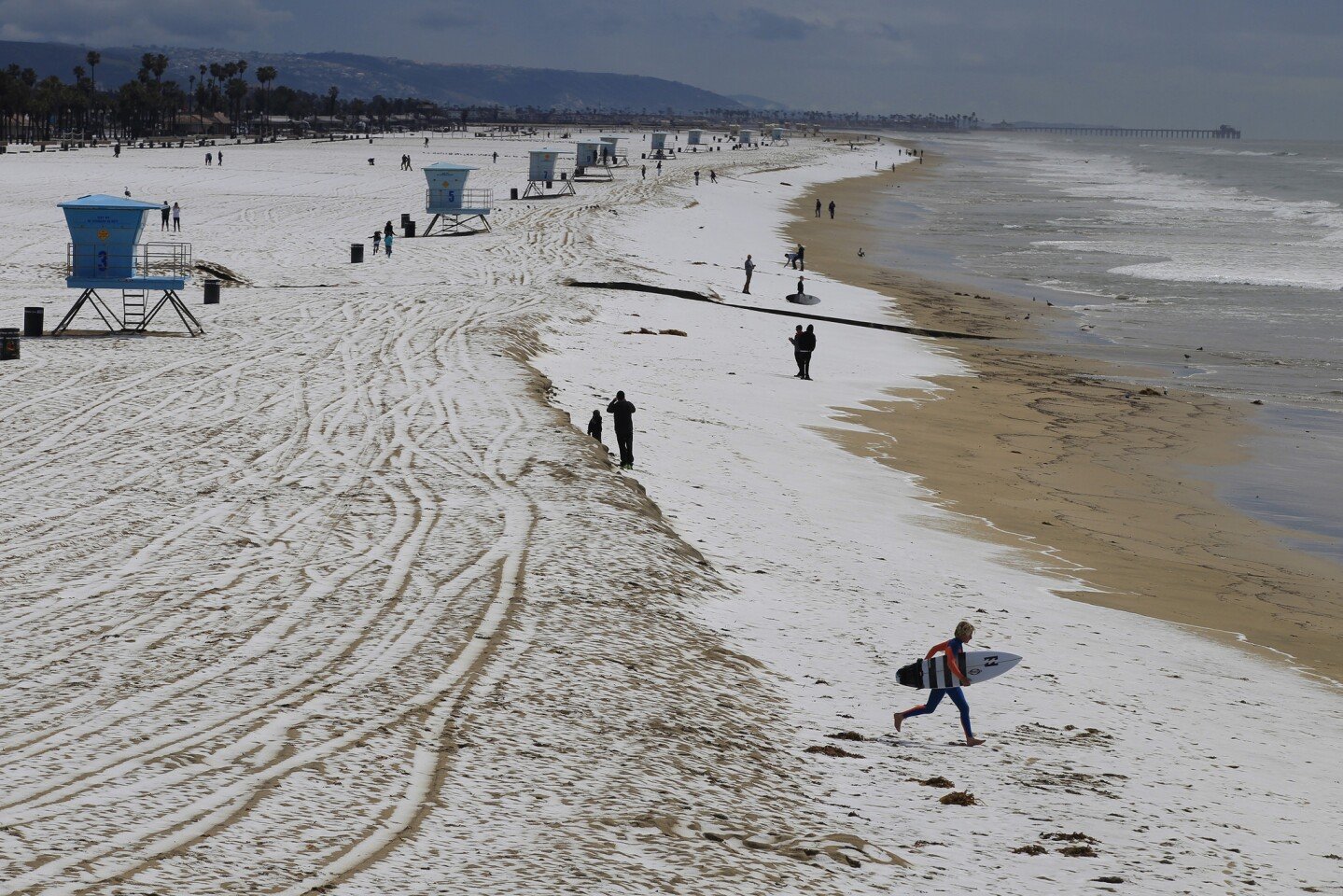 A surfer runs across the hail-covered sand in Huntington Beach.