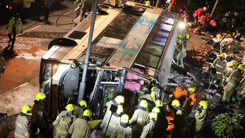 Crews work at the scene after a bus toppled near the town of Tai Po in Hong Kong's northern New Territories.