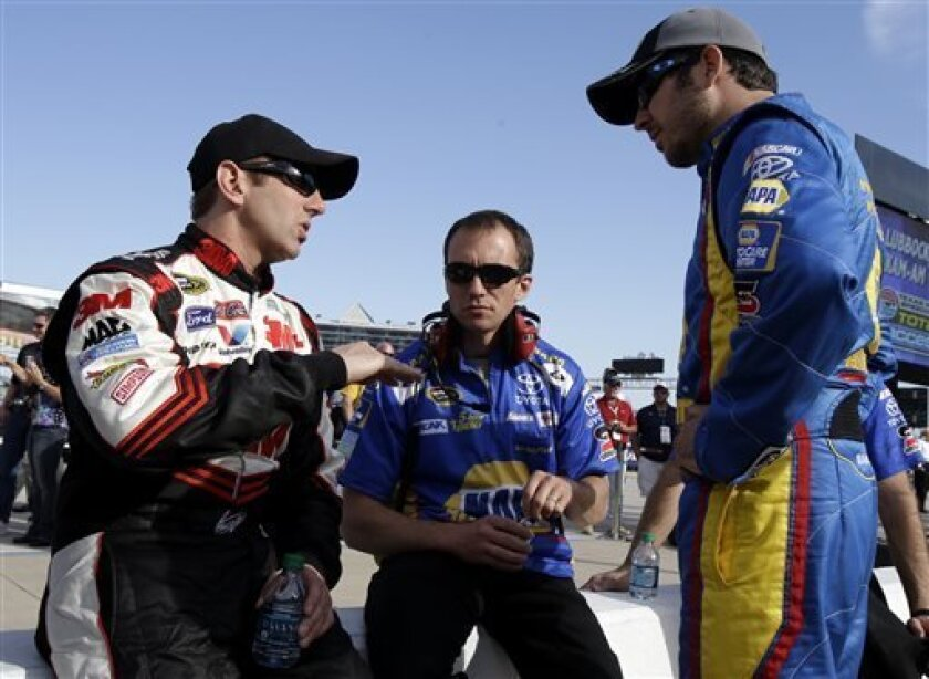 Greg Biffle, left, talks with Martin Truex, Jr., right, and an unidentified Truex team members during qualifying for the NASCAR Sprint Cup series NRA 500 auto race at Texas Motor Speedway, Friday April 12, 2013, in Fort Worth, Texas. Biffle is looking forward to a do-over in the new Sprint Cup car.
