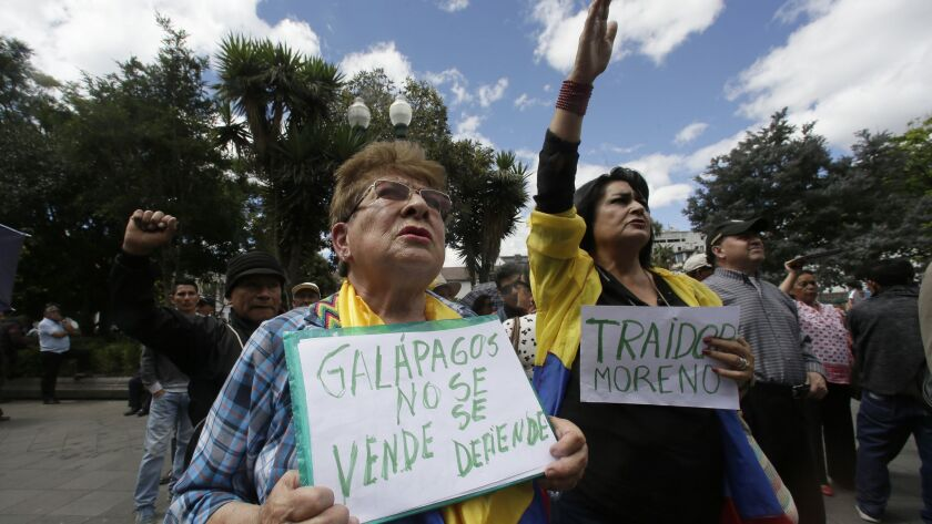 "A woman holds a sign with a message that reads in Spanish; ""Galapagos is not to be sold, but to be d"