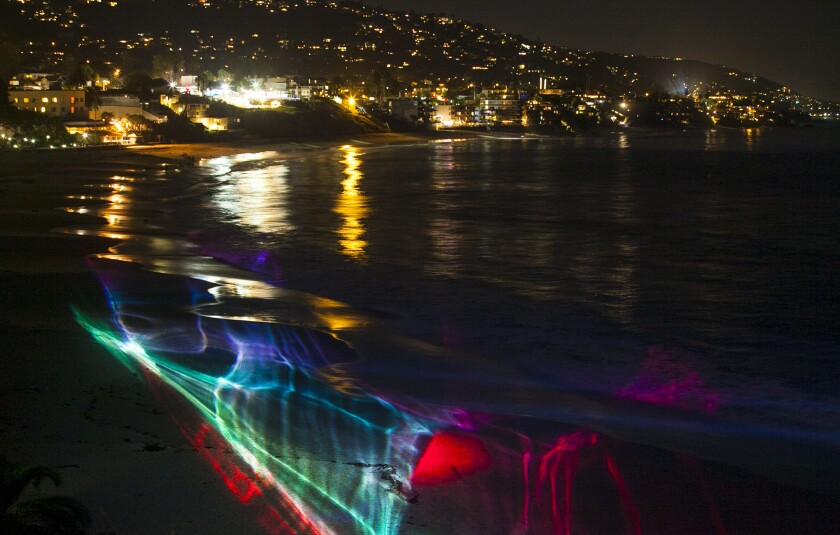 """Laser lights project on the sand and water during a rehearsal of """"Electric Light Blanket,"""" a laser light exhibit for the Laguna Art Museum's Art & Nature conference and festival."""