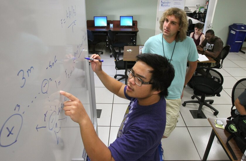 Physics tutor Steven Fisher, at right, watches student Ian Gallamoza write a lesson on a bulletin board at the Stem Center at Cal State San Marcos.