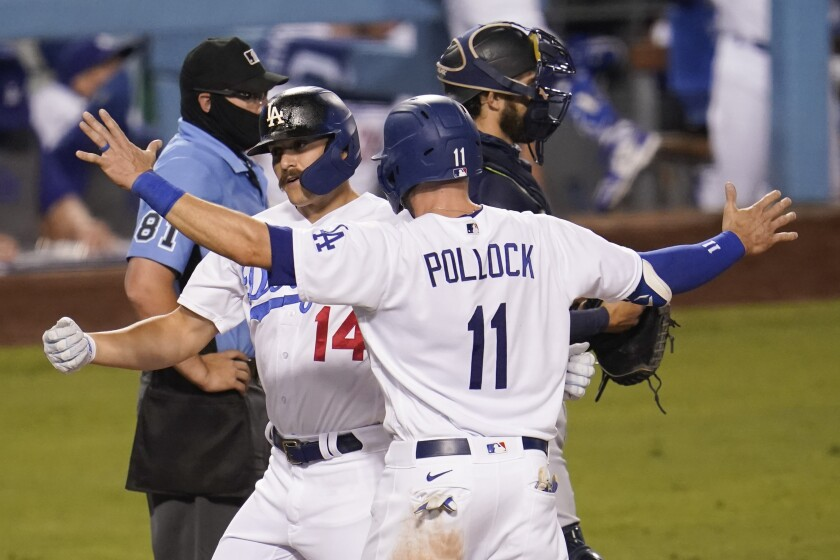 Kiké Hernández, left, celebrates his home run with A.J. Pollock in the Dodgers' game against the Seattle Mariners on Monday.