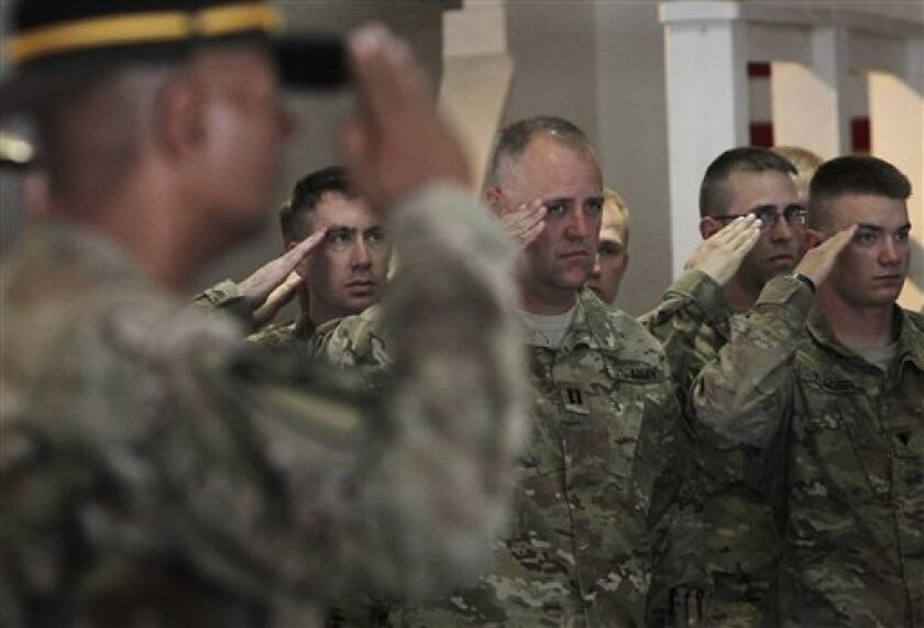 U.S. soldiers salute during a transfer of authority ceremony from Task Force Red Horse to Task Force Maverick at the U.S. base in Bagram, north of Kabul, Afghanistan, on Wednesday, July 13, 2011.  Task Force Red Horse is among two Cavalry regiments with the Iowa National Guard, and part of 10,000 U