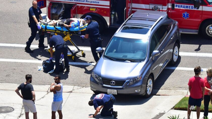A bicyclist is taken by stretcher after colliding with a Lexus that was heading east into a driveway